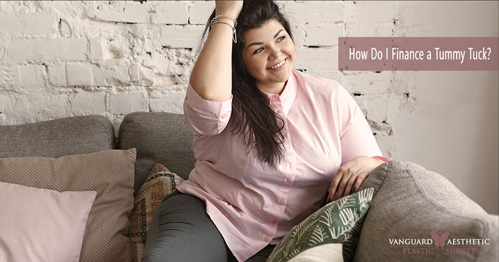 "Woman smiling and sitting on a couch, playing with her hair. ""How do I finance a Tummy Tuck""?"