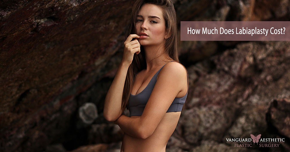 """Young model posing against ocean caves. """"How much does Labiaplasty cost?"""""""