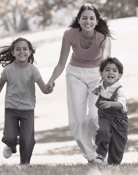 Mother running with children after full gamut makeover by Vanguard Plastic Surgery