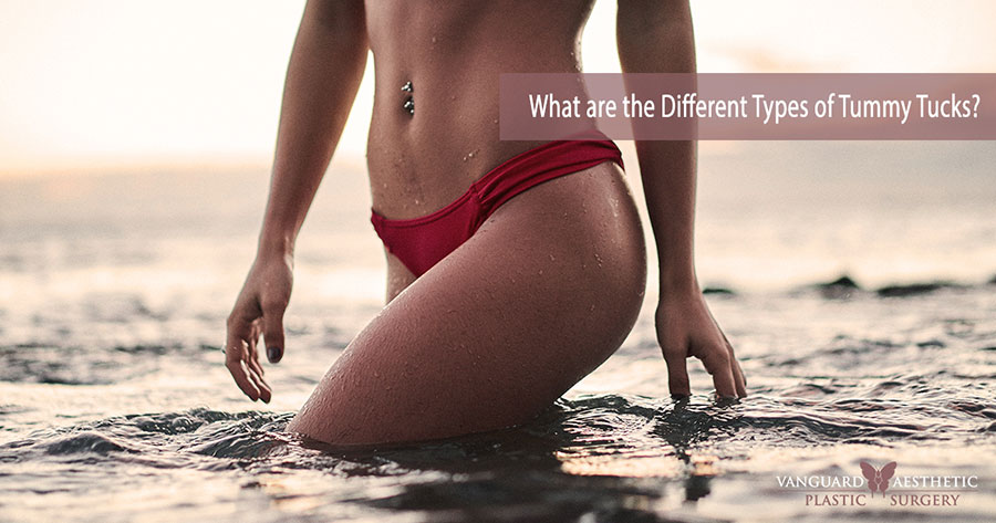 Woman's wading through the ocean and the camera shot is zoomed in on her flat tummy